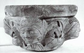 Column Capital. Carved with Faces at Corners, Bordered with Leaves.