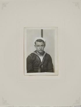 Sailor, seated in front of striped background