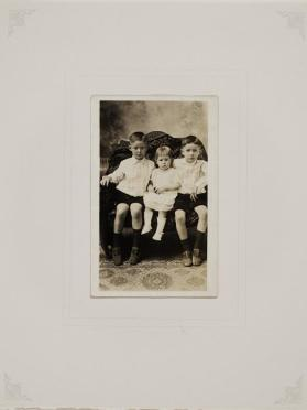Two little boys in matching outfits seated beside little girl on settee