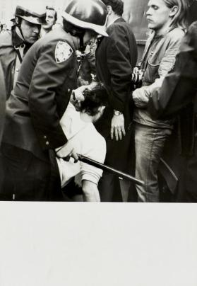 Police officer with baton holding demonstrator by her hair, Vietnam demonstration, NYC