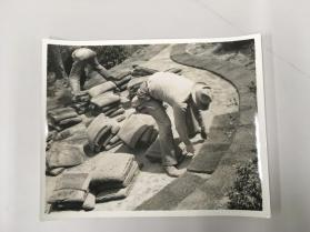Men placing grass tiles