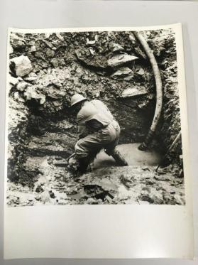 Construction worker digging mud, c.1955